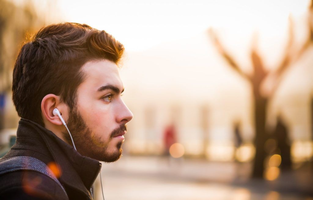 man listening to music in a park